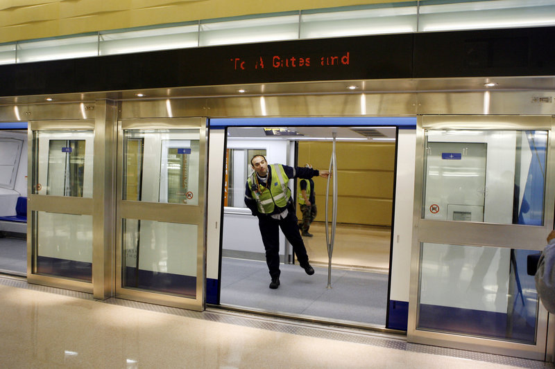 A worker looks out of a train car and through the open doorway of the glass security barrier at Washington Dulles International Airport. New York City is considering similar safety barriers after three people died on the tracks recently.