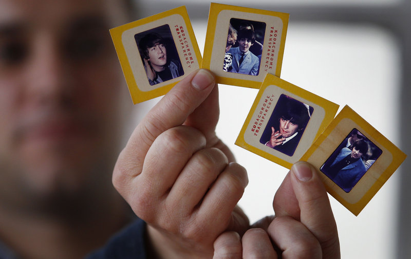 Auctioneer Paul Fairweather holds slides of The Beatles taken during their first tour of the United States in 1964. The rare color transparencies, taken by Dr. Robert Beck, are to be sold at Omega Auctions in Stockport, England, in March.