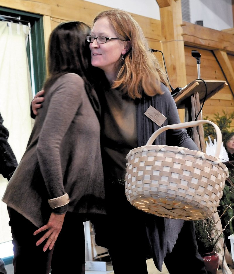 Maine Organic Farmers and Gardeners Association interim Executive Director Heather Spalding, right, accepts a Native American basket from Theresa Secord of Waterville during a memorial celebration of the late Russell Libby, a longtime leader of the organization, in Unity on Sunday.