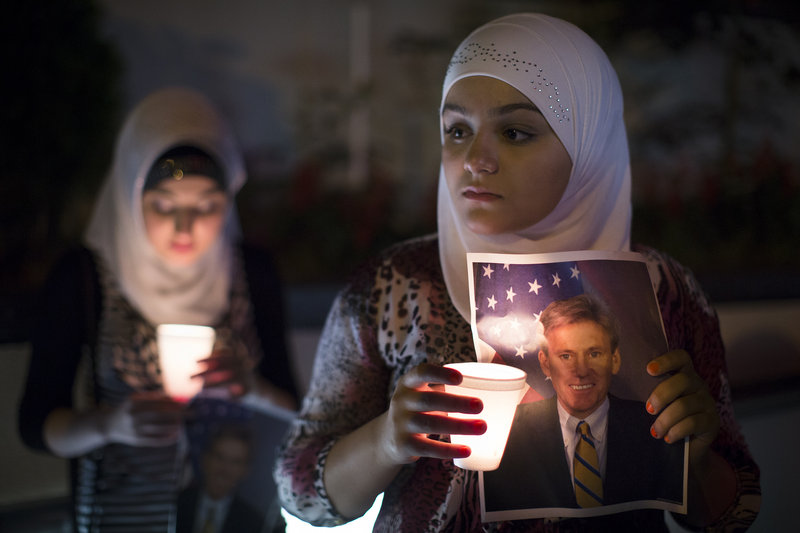 "A girl holds a photo of slain U.S. Ambassador to Libya Christopher Stevens at a vigil outside the Libyan Embassy in New York on Sept. 13. When Stevens was killed, Republicans soon doled out blame, but following the Newtown massacre, conservatives said that talk of new limits on firearms was an effort ""to 'capitalize on a tragedy,'"" a reader says."