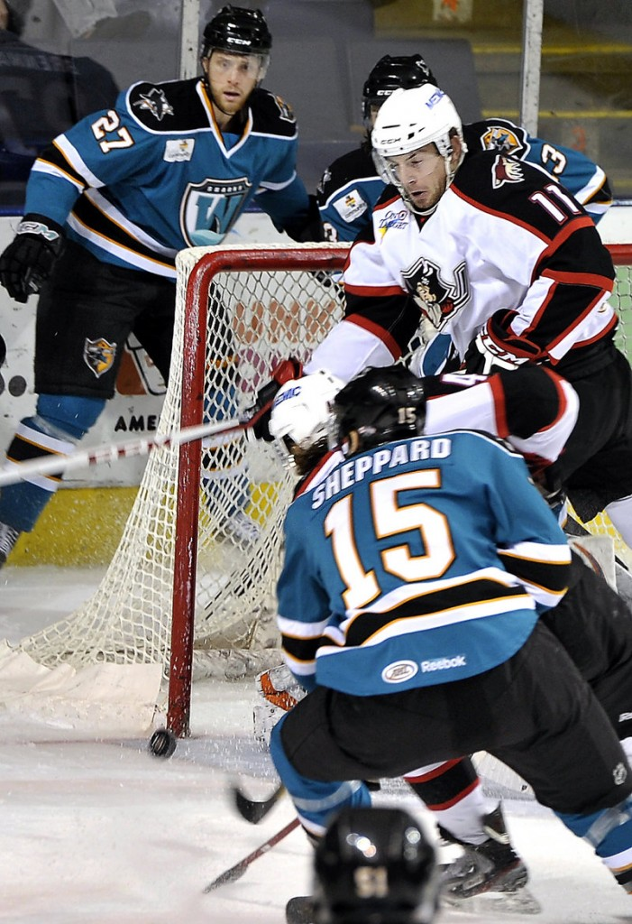 Chris Brown, 11, of the Pirates sets up a screen as a shot by Alexandre Bolduc slips by the post and heads toward the net in Portland's 7-3 win Tuesday night over the Worcester Sharks at the Cumberland County Civic Center.