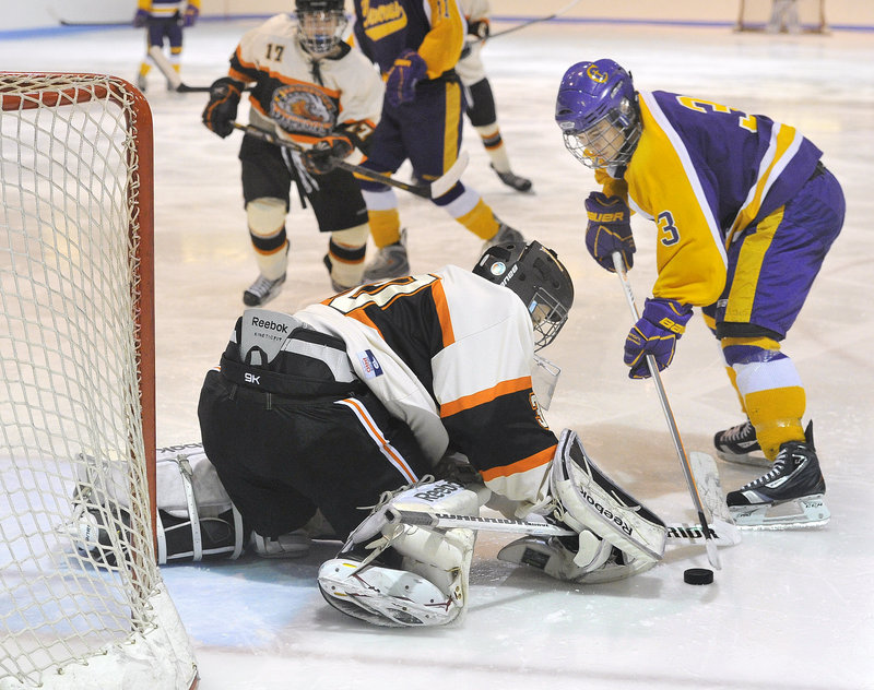Keegan Thomas of Cheverus looks to convert on a rebound as Brunswick goalie Blake Alexander attempts to cover the puck Wednesday during the third period of Cheverus' 4-1 victory at Watson Arena in Brunswick.