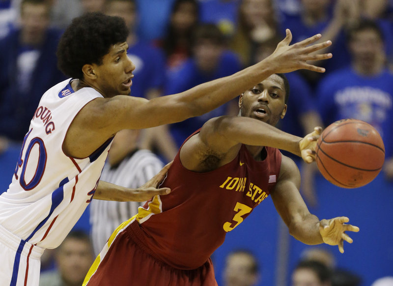 Melvin Ejim of Iowa State makes a pass while covered by Kansas' Kevin Young in Wednesday night's game at Lawrence, Kan. The Jayhawks won in overtime, 97-89.