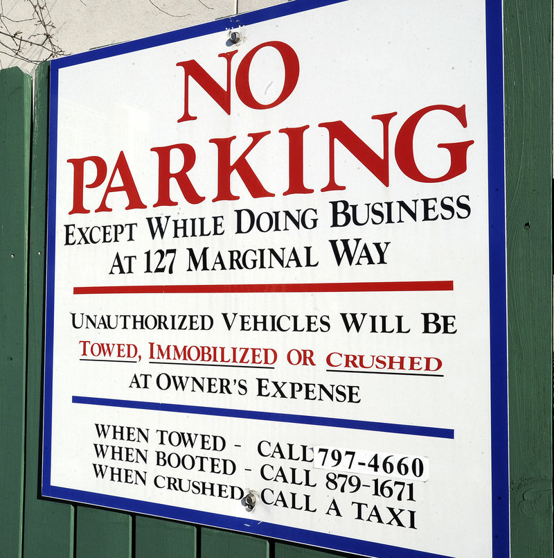 "A sign posted next to West Marine at 127 Marginal Way warns drivers not to park in the lot unless they're visiting the boating supply store or other businesses at the address. Trader Joe's shoppers who park there may find their car towed or booted – the ""crushed"" threat was just a joke."