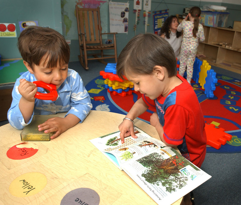 Children share a book at Head Start on Cumberland Avenue in Portland in 2003. Head Start was one of the programs that experienced funding cuts when last spring's state budget was passed. This hit Maine women hard, since they are more likely than men to be single or custodial parents, say the heads of two nonprofits.
