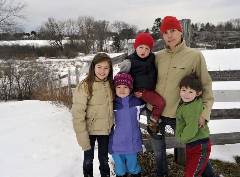 Sarah Russell poses Friday with her children, from left, Olivia, 9; Annie, 7; George, 3; and Charles, 5, in Cumberland. Russell supports hunting and gun ownership rights and allows hunting on her property, but she also believes in tighter restrictions on assault weapons and high-capacity magazines.