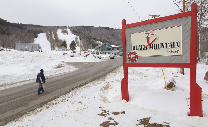 A snowboarder walks up the main access road to Black Mountain, long a local attaction that now is marketing itself for an expanded clientele.