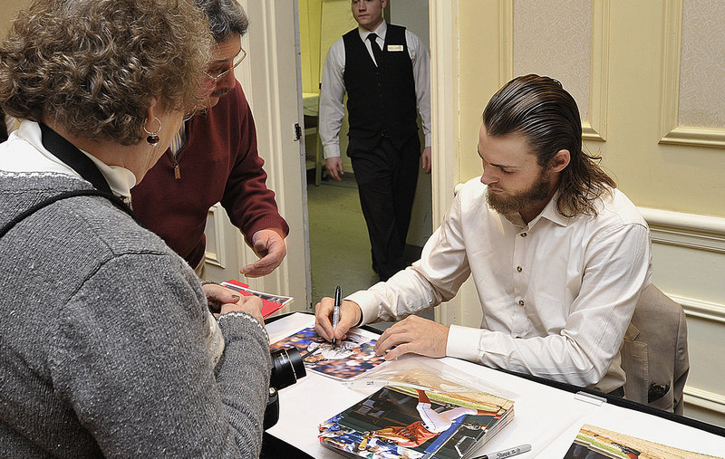 Josh Reddick, who hit 32 home runs last season for the Oakland Athletics, signs a photo Friday night at the Sea Dogs' annual banquet, Reddick played for Portland in the 2008 and 2009 seasons.