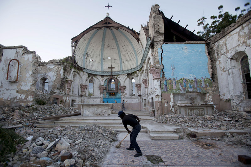 A man sweeps an exposed tiled area of the earthquake-damaged Santa Ana Catholic church, where he now lives, in Port-au-Prince, Haiti, on Saturday. Haitians recalled Saturday the tens of thousands of people who lost their lives in the devastating 2010 earthquake. More than 350,000 people still live in displacement camps.