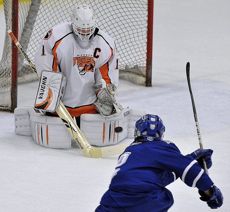Biddeford goalie Jon Fields holds his ground and stops a shot by Evan Gosselin of Lewiston during Lewiston's 3-1 victory Saturday at Biddeford Ice Arena. Fields came up with 40 saves.