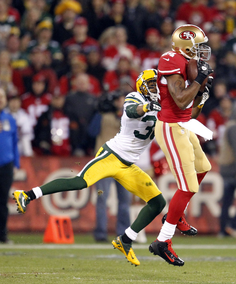 Randy Moss, now a role player with the San Francisco 49ers, snags a pass against Green Bay Packers cornerback Tramon Williams in the first half.