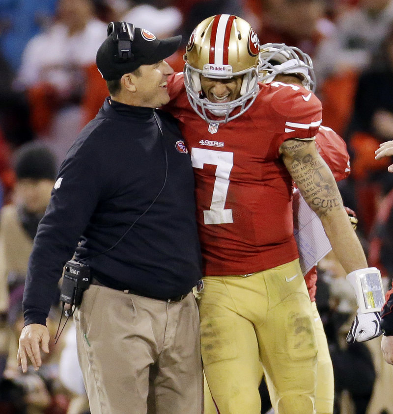 San Francisco Coach Jim Harbaugh celebrates with Colin Kaepernick after the quarterback's 56-yard touchdown run against the Green Bay Packers during the third quarter of Saturday's game, won by San Francisco.