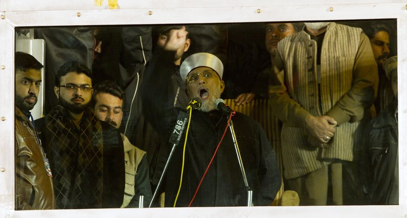 Behind bulletproof glass, Pakistani Sunni Muslim cleric Tahir-ul-Qadri, addresses his supporters about government corruption.