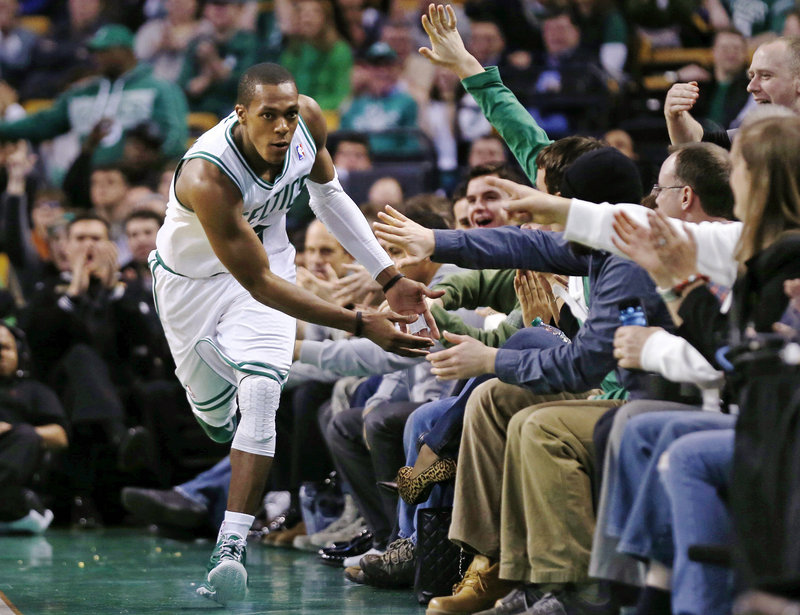 Boston's Rajon Rondo has courtside supporters with high-fives at the ready after he scored two of his 17 points during the Celtics' 100-89 win at Boston on Monday.