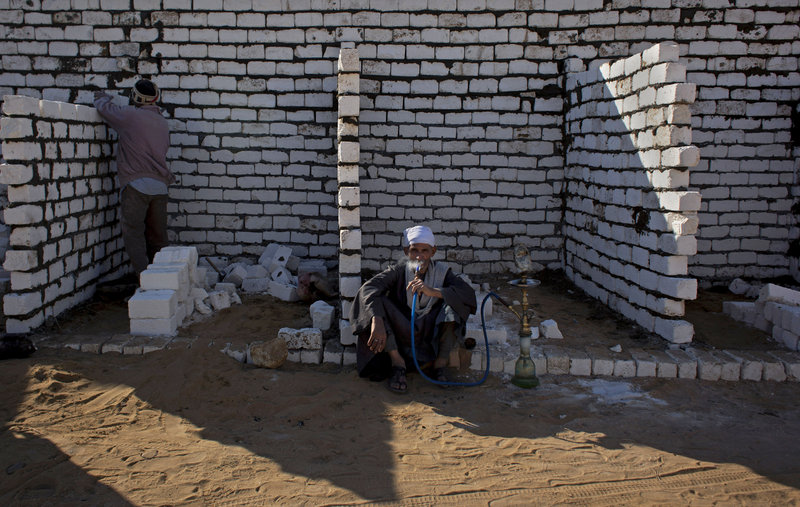 An Egyptian laborer works as his employer smokes a water pipe at the local cemetery that is spreading toward Egypt's first pyramids and temples.