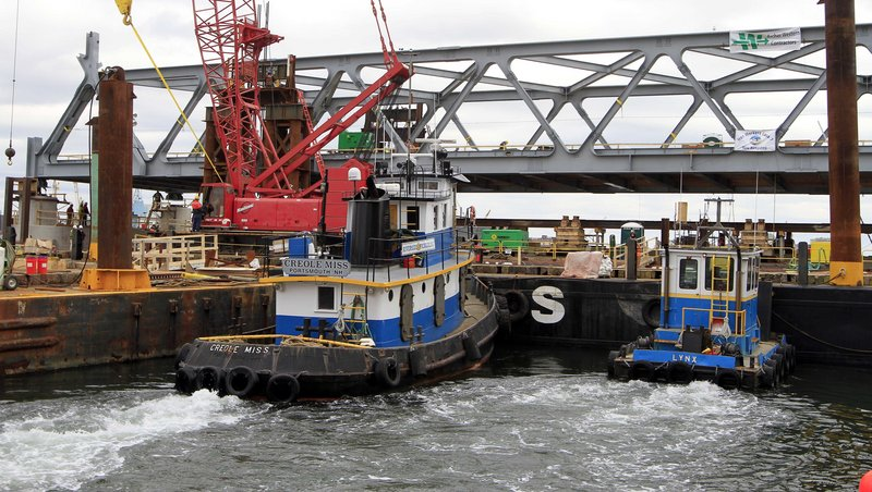 Tug boats are used to position a new 2 million-pound section of the Memorial Bridge Tuesday Jan. 15, 2013 in Portsmouth, N.H. The new bridge will connect Maine and New Hampshire and is expected to open in July. (AP Photo/Jim Cole)