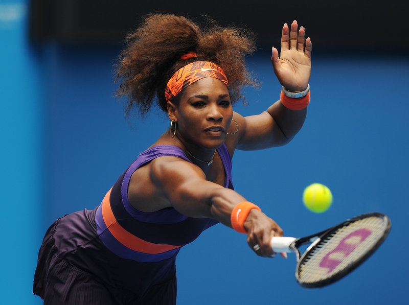 Serena Williams hits a backhand return in Thursday's second-round match with Garine Muguruza. Williams, nursing an injured ankle, advanced, 6-2, 6-0.