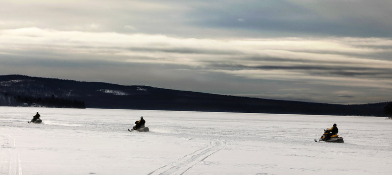 Snowmobilers head across a cove on Rangeley Lake in Rangeley on Jan. 12.