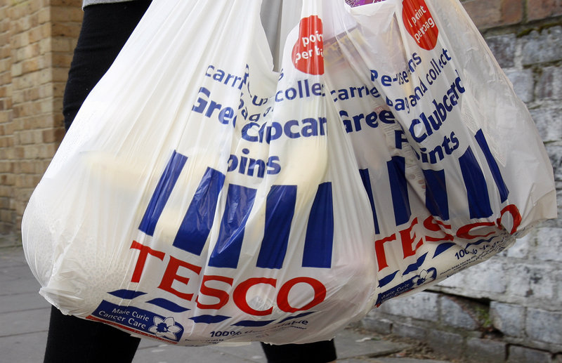 A shopper carries Tesco bags in London. An Irish food safety watchdog says it has found traces of horse DNA in burgers sold by some of the country's biggest supermarkets.