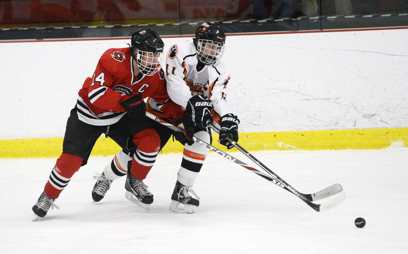 Trevor Murray of Scarborough, left, races Niklas Lemieux of Biddeford to the puck Thursday night. Scarborough improved to 9-1 by collecting its fourth straight shutout, winning 3-0 at the Biddeford Ice Arena.