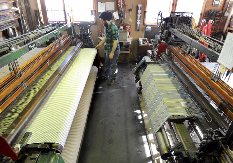 Ryan Benoit watches over two of the looms at the Brahms Mount factory.