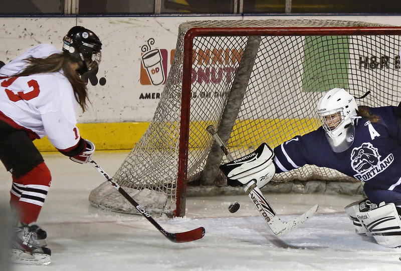 Madison O'Reilly of Scarborough sneaks the puck past Portland/Deering goaltender Leanne Reichert to score the final goal of the game Saturday as Scarborough came away with a 7-0 victory at the Cumberland County Civic Center.