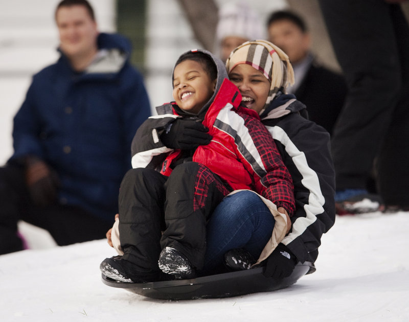 Sahra Atoor, 17, and brother Salmaan, 5, of Portland share the ride Saturday at the festival in Payson Park.