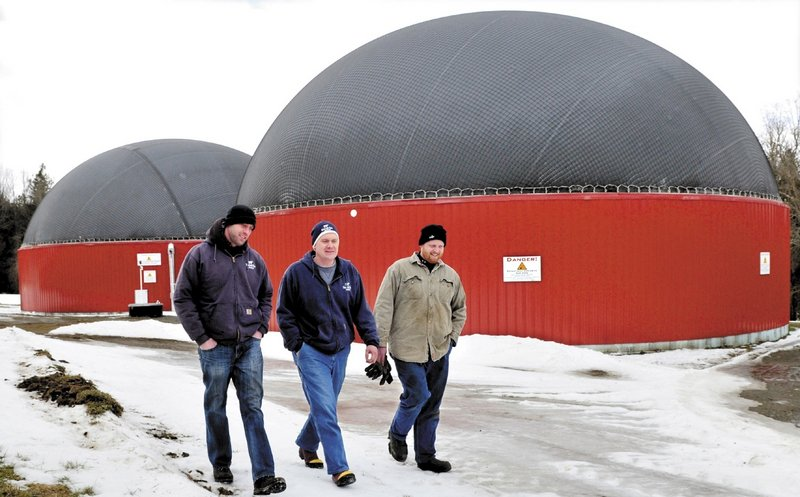 Adam Wintle, left, Travis Fogler and John Wintle walk past the digester buildings where food waste and cow manure are mixed to produce gas that powers a generator for electricity.