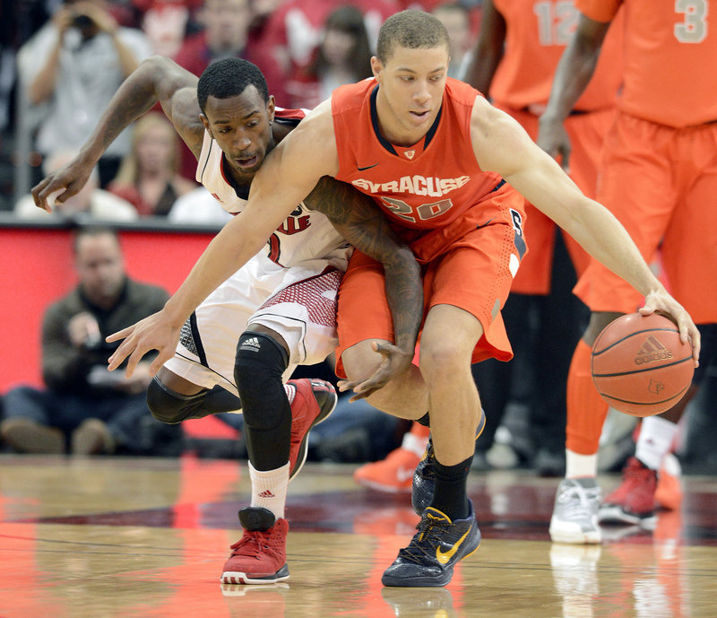 Brandon Triche of Syracuse protects the ball from Louisville's Russ Smith during Saturday's game at Louisville, Ky. Triche scored 23 points to help the Orange secure a 70-68 victory.