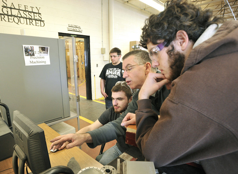Marc Cadorette, an instructor at the Biddeford Regional Center of Technology, works with students in the machine tool technology class to use a computer program that automates the drilling machine.