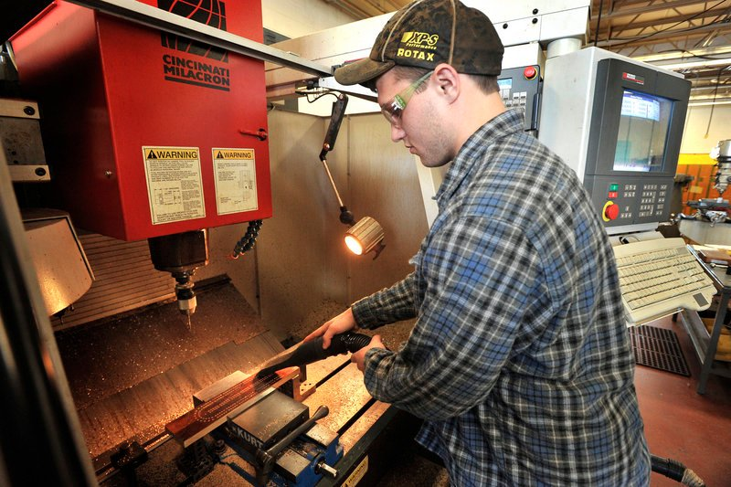 Student Jeremy Lambert vacuums sawdust from a drilled board before removing it from the computerized drill machine.
