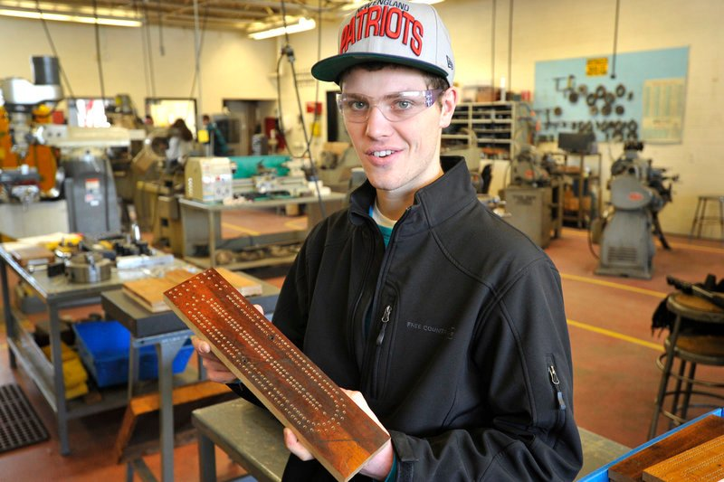 Patrick Wilson, a student at the Biddeford Regional Center of Technology, shows a cribbage board that was drilled by a computerized machine.