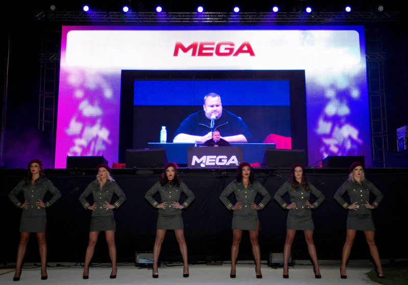 Kim Dotcom appears on a screen Sunday at the launch of his new file-sharing website, Mega, at his mansion in Auckland, New Zealand. The German-born entrepreneur is under indictment for alleged piracy on his former site, Megaupload.