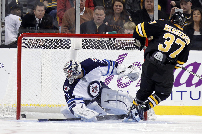 Patrice Bergeron of the Bruins slips a shot between the pads of Winnipeg goalie Ondrej Pavelec to score in the shootout Monday at TD Garden in Boston. The Bruins won their second straight game, beating the Jets 2-1.