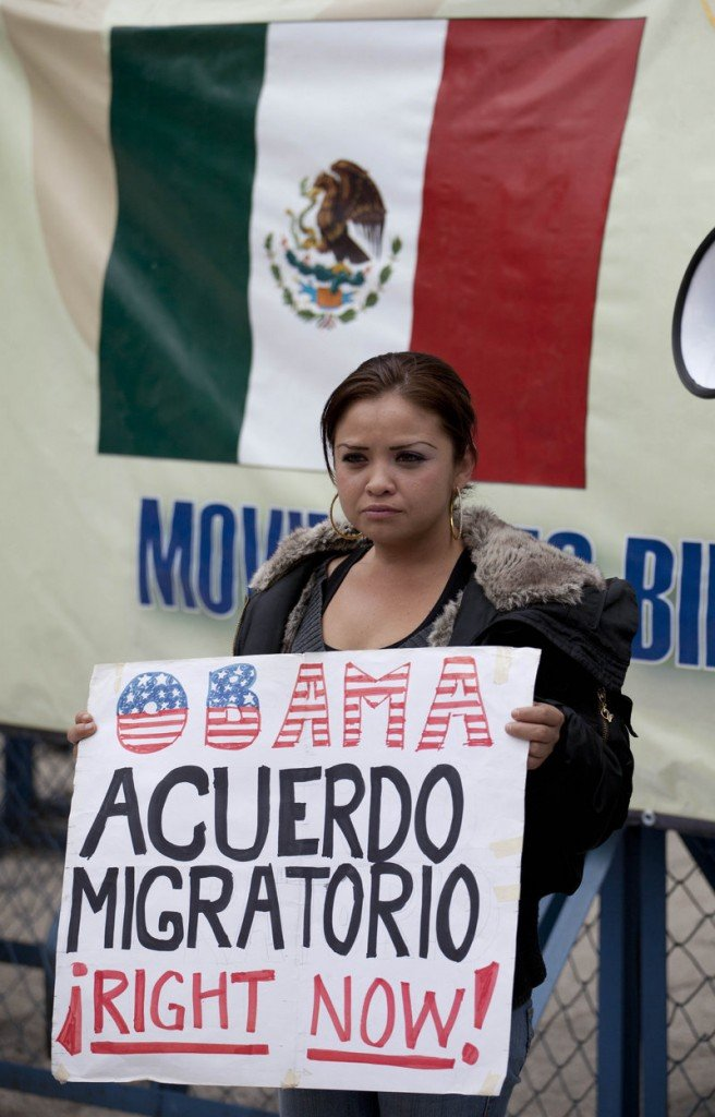 "A migrants' rights activist holds a sign that reads, in Spanish, ""Obama, migration agreement right now!"" outside the U.S. embassy in Mexico City."
