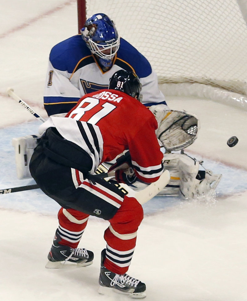 Blues goalie Brian Elliott makes a save on Chicago's Marian Hossa in Tuesday night's game at Chicago. The Blackhawks won, 3-2.