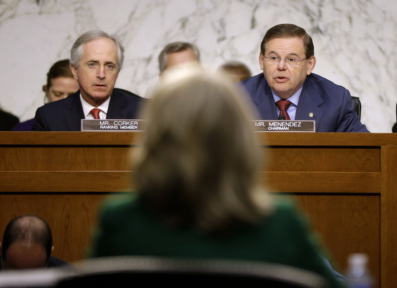 Secretary of State Hillary Rodham Clinton, back to camera, tangles with the Senate Foreign Relations Committee's Sen. Bob Corker, R-Tenn., left, and Sen. Robert Menendez, D-N.J.