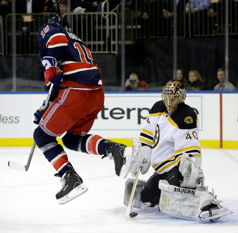 Jeff Halpern leaps to allow the puck to reach Bruins goalie Tuukka Rask, who made the second-period save Wednesday in New York. The Bruins lost for the first time this season.