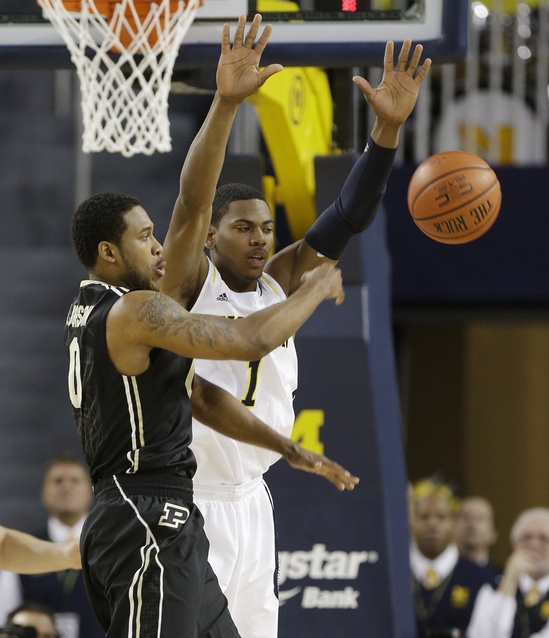 Terone Johnson of Purdue, left, passes the ball Thursday night while guarded by Glenn Robinson III of second-ranked Michigan during Michigan's 68-53 victory.