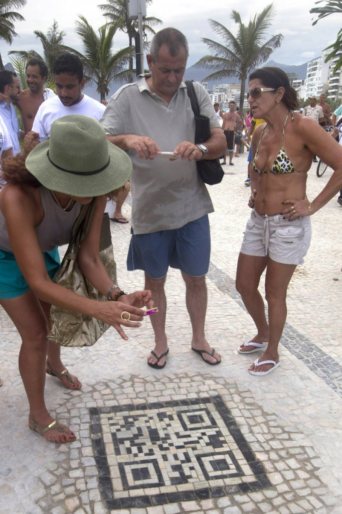 A woman holds a cellphone over a QR code made of black and white stones on the sidewalk near the beach in Rio de Janeiro, Brazil, on Friday. The QR codes are being placed at tourist spots and can be scanned with a mobile device for information about the site.