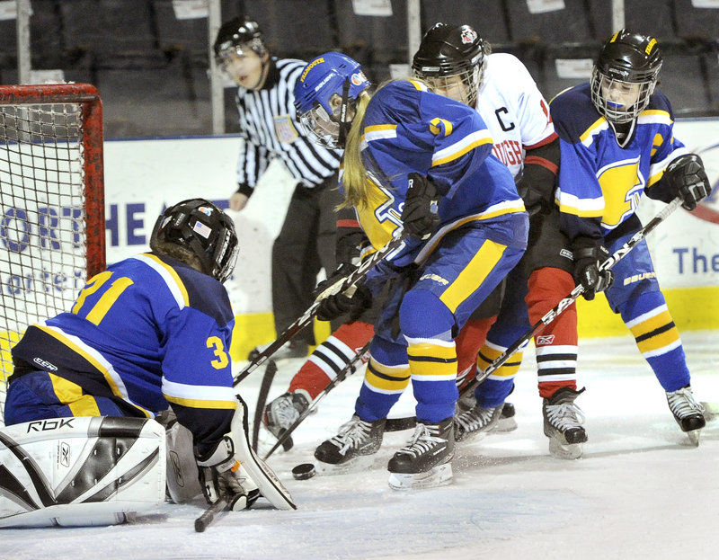 Falmouth goalie Hillary Nash keeps the puck in sight as Alta Farrell and Abby Payson keep Sarah Martens away.