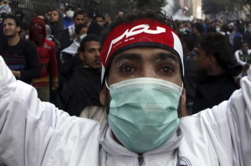 "A protester opposing Egyptian President Mohammed Morsi gestures with a head band that reads ""Egypt"" at riot police during Saturday's clashes near Tahrir Square in Cairo."