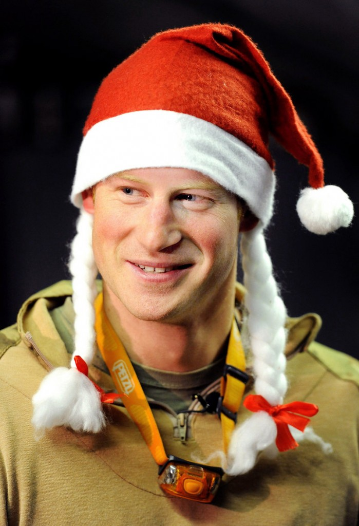 In a Dec. 12, 2012, file photo, Britain's Prince Harry wears a Santa hat as he shows a media crew his sleeping area at the VHR (very high readiness) tent, close to the flight-line, at Camp Bastion in southern Afghanistan. During Prince Harry's 20-week deployment in Afghanistan, he served as an Apache helicopter pilot with the Army Air Corps.