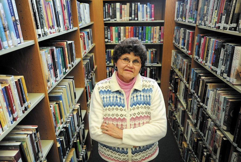 Carol Cooley, a librarian at the Oakland Public Library, stands among some books available for checkout Thursday. Cooley recently called local police about a delinquent book borrower who had failed to return $200 in books.