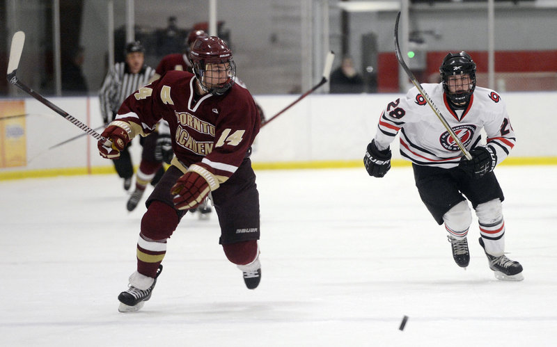 Thornton Academy's Drew Lavigne, left, looks for the fast-approaching Jacob Gross of Scarborough, as the two race for the puck during Scarborough's 4-3 win Monday afternoon at the MHG Ice Centre in Saco.