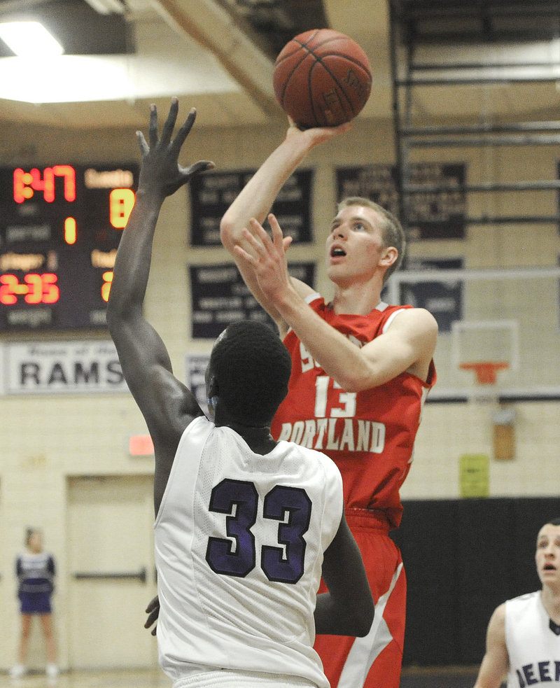 Tanner Hyland, who scored a game-high 22 points for South Portland, finds room to loft a shot over Labson Abwoch of Deering.