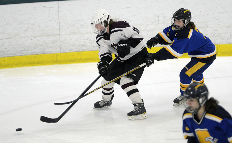 Mary Morrison of Greely goes after the puck Wednesday night while being chased by Abby Payson of Falmouth. Greely won, 5-1.