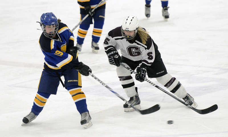 Martina St. Angelo of Falmouth passes the puck Wednesday night as Meg Finlay of Greely skates in to apply pressure. Greely increased its undefeated run to 11 games and improved to 14-2-1 by coming back for a 5-1 victory.