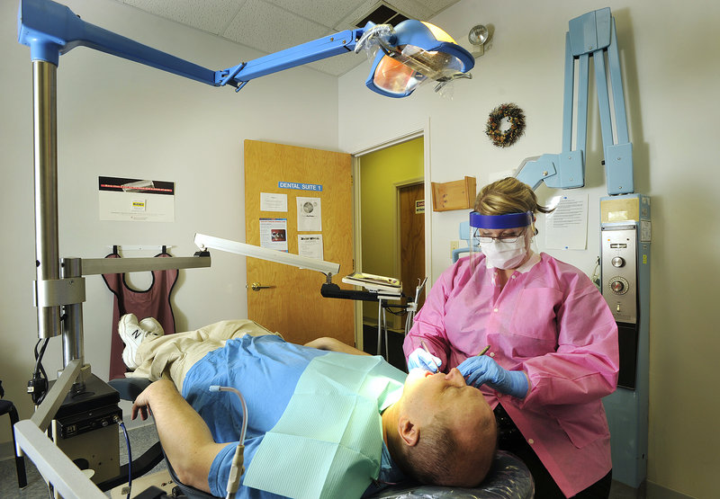 On Thursday, dental hygienist Torey Richard cleans the teeth of patient Rick Hagan, 45, of Bath, who has bipolar disorder, at the state-funded dental clinic on Preble Street in Portland.