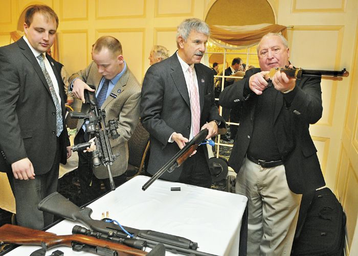 Rep. Matt Pouliot, left, Rep. Corey Wilson and Sen. Roger Katz, all R-Augusta, look over a table of weapons with Richard Beausoleil, far right, of Kennebec County Emergency Management Agency, on Thursday at the Senator Inn and Spa in Augusta.